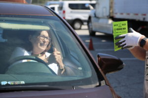 Though her rolled down car window, an attendee speaks with the staff member taking her order.